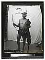 [Portrait of an Indian man with ceremonial headdress standing in front of a drape]