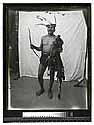 [Portrait of an Indian man with ceremonial headdress standing in front of a drape #2]