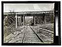 [Railroad tracks converging under a wood bridge]