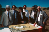 Six people standing around a model of the proposed Contra Costa Campus at the groundbreaking ceremony