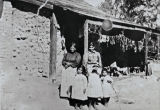 Margarita Bernal, Rosa Cota and children in front of Margarita's adobe house at Zanja de Cota : beef jerky is drying in the background : 1890s.