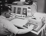 A man utilizing an IBM 1620 Data Processing System.