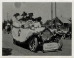 Upland Photograph Events; Parade: Gerry Millinery advertised by 8 women all wearing hats, seated in a decorated automobile / Melicent Arner