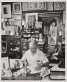Guy Bogart in 1955, sitting and working at his desk at 545 Euclid Ave.