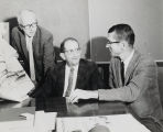 Ralph Shaw, Dale Wren, and Floyd Erickson looking at artist's renderings of campus building