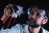 Bearded man holding a beaker