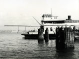 As the Coronado-San Diego Bay Bridge nears completion in the background, one of the last ferries to transport automobiles across the San Diego Bay waits for departure, circa 1969