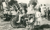 "George and Carolyn Barker with bicycle and doll carriage during the """"Children's Floral Parade"""" in Banning, California"