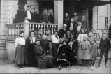 Photograph of teachers and schoold children standing on porch of Placentia Union Grammar School.