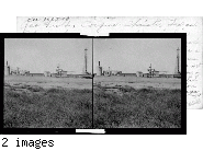 Gas Field, Corpus Christi, Texas. About the center of this view is seen an apparatus with many wheels for the purpose of opening valves.  This is producing gas well & is commonly known as a x-mas tree.  This sell produces dry & wet gas, also oil & salt water, hence the purpose of the tanks to the left is to separate the water from the oil & the round, upright contraption connected by pipe with the little house is for separating the dry from the wet gas. To the extreme right you will see a new well being drilled. #41