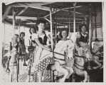 The 1949 Cherry Festival Queen and her Court riding a merry go round.