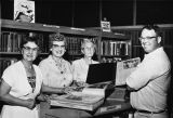 Four people at the Reference Desk of the Banning Public Library in Banning, California
