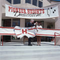 120 mm Direct Positive of Ellis E. McCune and unknown girl (student) cutting the ribbon at the Pioneer Heights Dedication Ceremony.