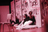 Performance: three actors sitting in front of graffiti backdrop