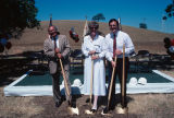 Three unknown persons posing for the ceremonial groundbreaking with shovels
