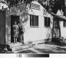 Photograph of woman and teenage boy in front doorway of Keppler Grove unit