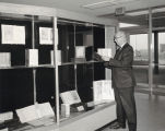 A photograph of Library Director Floyd Erickson handling items from the DeBellis Collection on loan from San Francisco State University.