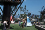 [Children playing on playground with teepees slide].