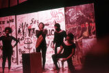 Play performance with four actors in front of a spray painted backdrop