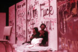 Play performance: two actors or dancers sitting against graffiti backdrop