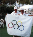 [Philip J. Reilly and Ziggy Wilczynski holding Olympic flag photograph].