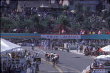 [1984 Olympics Men's Cycling Road Race showing the cyclists as they complete a lap near the finish line slide].