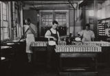 Photograph of filling cans inside the J.E. Taylor & Co. cannery