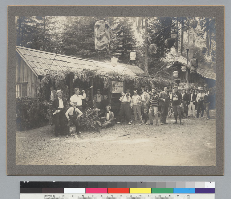 Men in front of Dew Drop Inn, three are blowing horns