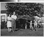 Photograph of man spraying two children with a garden hose while a woman looks on