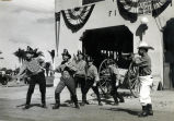 "Chief Thompson and other Coronado firefighters pulling a ""horse drawn hose cart"" during the Hotel del Coronado's 50th anniversary celebration, 1938"