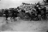US Navy sailors practice amphibious maneuvers with cannons on beach in front of Hotel del Coronado, c. 1918