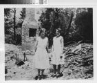 Clarissa Young Byrnes and Dorothy Greg in front of a burned home