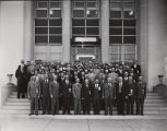 Photograph of group of men in front of building
