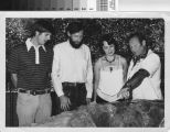 [Four people looking at whale fossil photograph].