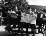 [Male students sitting outside, reading The weekly torch]
