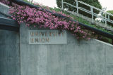 Slide of University Union sign on side of building with flowers.