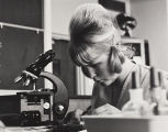 A woman looking through slides near a microscope in a science lab.