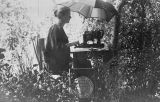 Photograph of Anne Hadden on library grounds writing a paper for American Library Association