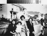 Three women and one child beside car on Harmon Street, 1950