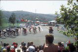[1984 Olympics Women's Cycling Road Race with cyclists turning corner and hills in background slide].