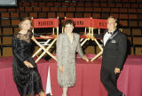 Two women and a man in formal attire standing in front of personalized director's chairs.
