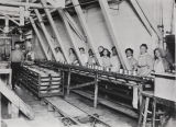 Photograph of workers on the assembly line filling cans inside the J.E. Taylor & Co. cannery