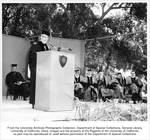 Charter Day, Chief Justice Earl Warren at the podium. Seated behind him were the Regents, with John E. Canaday, Lieutenant Governor Glenn M. Anderson, John S. Watson, and Mrs. Edward H. Heller in view.