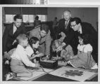 Photograph of several German educators visiting with children at a public housing project in Los Angeles