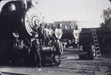 A crew of railroad men posing in front of steam locomotives in Beaumont, California