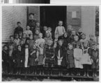 "Class portrait taken on steps of ""Old Tin Schoolhouse"", ca. 1906-1908."