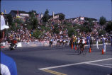 [1984 Olympics Men's Cycling Road Race showing cyclists turning a corner in front of a slope filled with spectators slide].