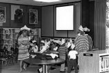 Library workers and children in the children's room at the library